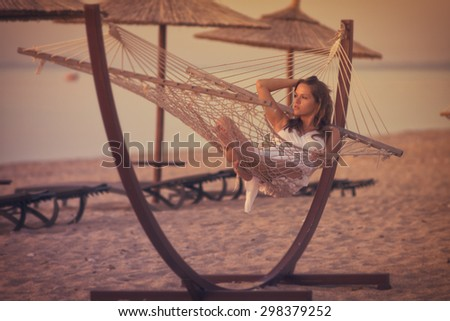 Relaxing in a hammock / Beautiful young women resting in a beach, vintage style photo with custom white balance, color filters, soft focus effect, and some fine film grain added - stock photo