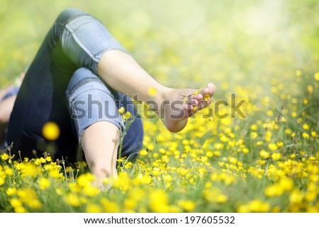 Relaxing in a meadow full of buttercups in the summer sun - stock photo