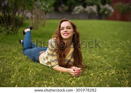 Relaxing in grass. beautiful young woman smiling while lying on the green grass - stock photo