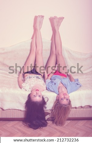 relaxing legs up: 2 glamor blond & brunette sexy girlfriends with red lips having fun posing lying in bed together & looking at camera on light copy space background, portrait - stock photo
