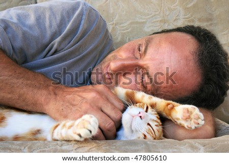 Relaxing man and cat on sofa. - stock photo