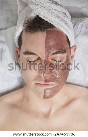 relaxing man with a mud mask on this face - stock photo