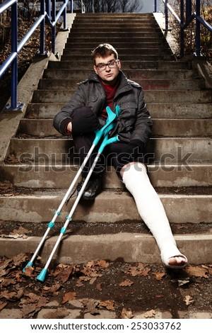 Relaxing man with broken leg in gypsum  - stock photo