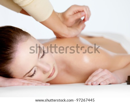 Relaxing massage on a back for young beautiful woman - white background - stock photo