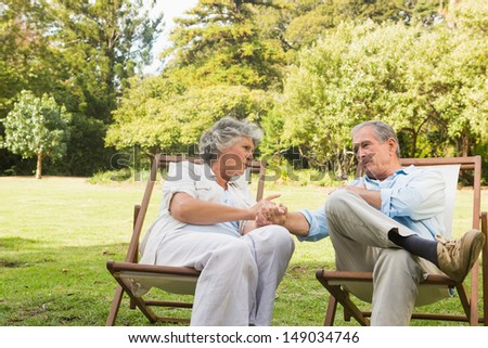Relaxing mature couple sitting on sun loungers and talking on a sunny day - stock photo