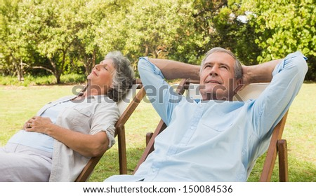 Relaxing mature couple sitting on sun loungers in the park in sunshine - stock photo