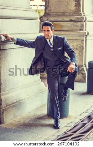 Relaxing on street. Dressing in dark blue three pieces suit, necktie, vest,  leather shoes, bending a leg, stretch a arm,  a handsome, middle age businessman sitting on street,  waiting for you  - stock photo