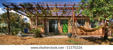 Relaxing outdoor setting under a pergola - stock photo