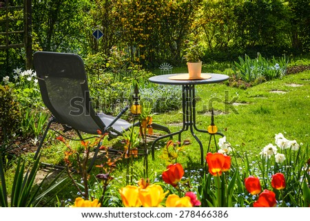 Relaxing place-table and deck chair in flowering garden.