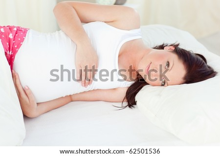 Relaxing pregnant woman sleeping in her bed at home - stock photo
