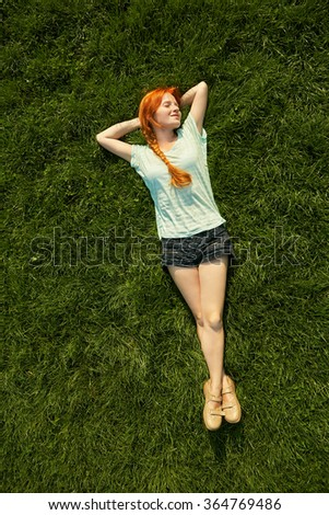 relaxing redhead girl lying on the grass. woman relaxation outdoor