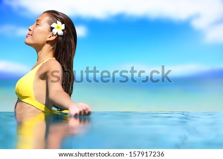 Relaxing serene woman at travel spa resort pool. Happy blissful asian young woman in bikini enjoying sun on holidays on Hawaii. - stock photo