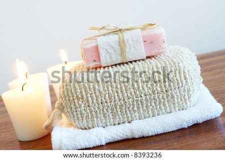 Relaxing spa scene with exfoliating body sponge, handmade soap, white face cloth and candles in the background - stock photo