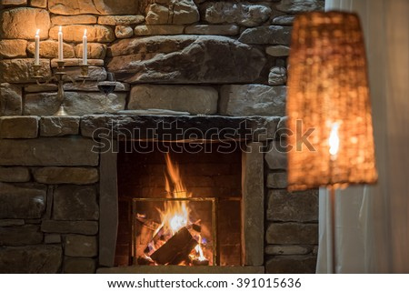 Relaxing stone fireplace with candle and red vine - stock photo