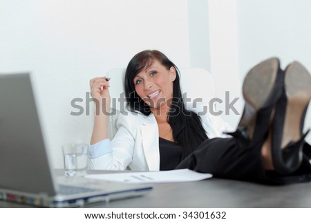 Relaxing successful business woman with feet on desk smiling and holding pen