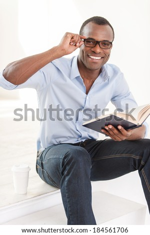 Relaxing with his favorite book. Cheerful young African man in blue shirt holding a book and looking at camera while sitting on stairs with a cup of coffee near him - stock photo