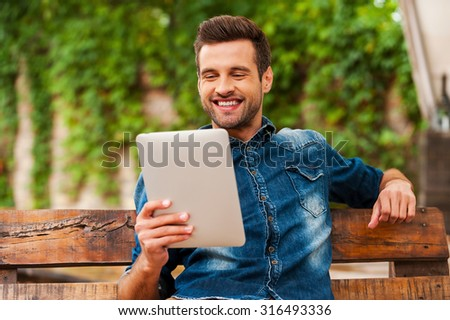 Relaxing with his new tablet. Happy young man holding digital tablet and smiling while sitting on the wooden bench outdoors - stock photo