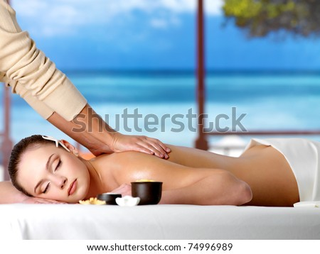 Relaxing woman in a resort having spa healthy massage - horizontal - stock photo