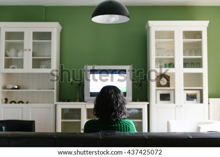 Relaxing woman watching tv in living room. - stock photo