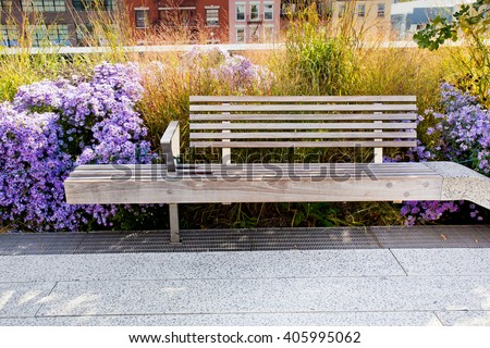 Relaxing wooden bench surrounded by wildflowers along The High Line in New York City - stock photo