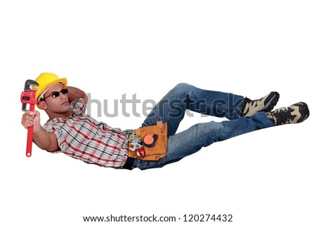 Relaxing workman with a wrench - stock photo
