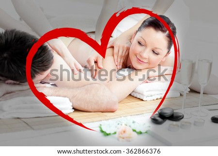 Relaxing young couple enjoying a back massage against heart - stock photo