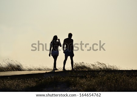 Relaxing young couple silhouette. Man and woman walking by a pathway on a beach. - stock photo