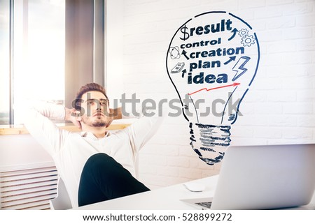 Relaxing young man with creative light bulb drawing at workplace. Business process concept