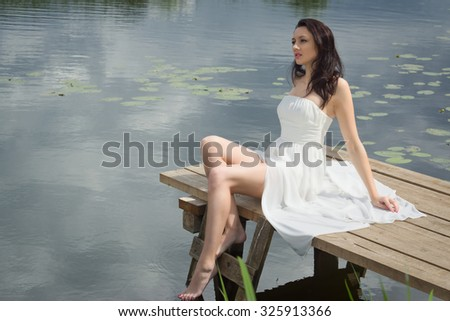 Relaxing young woman on wooden pier at the lake in summer day