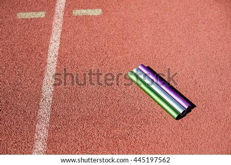 Relay baton on running track in stadium - stock photo