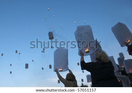Releasing hot air lanterns of luck - stock photo