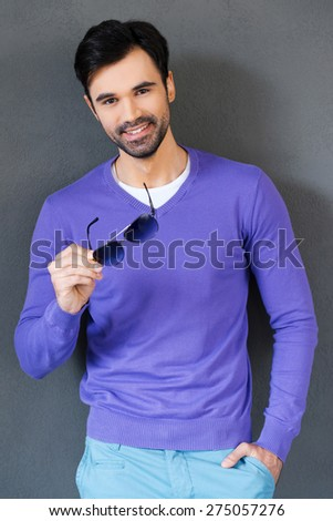 Reliable smile. Handsome young man holding eyewear and smiling at camera while standing against grey background - stock photo