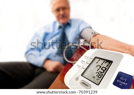Relieved senior man in shirt and tie (businessman or teacher) with a low blood pressure reading on the monitor. On white.