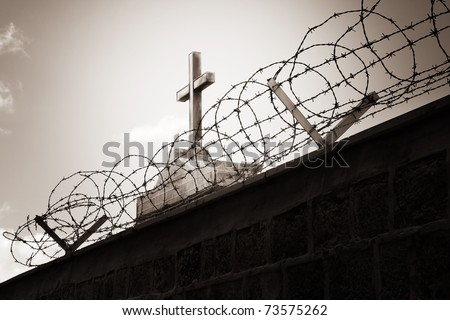 Religion and war concept - cross behind barbed wire - stock photo