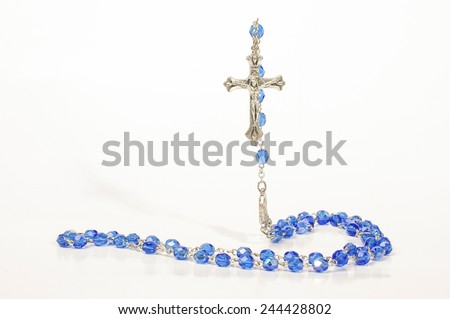 Religion concept flying cross over rosary - stock photo