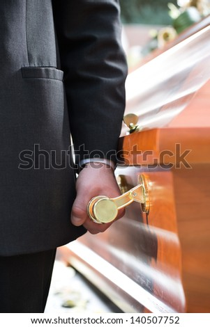 Religion, death and dolor - coffin bearer carrying casket at funeral to cemetery - stock photo