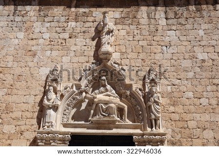 Religious carving of the dead Christ lying in the arms of His mother, Mary above a doorway in Dubrovnik, Croatia. - stock photo