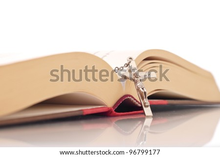 Religious Concept image with Rosary Cross Leaning on Open Bible - stock photo