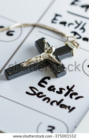 religious cross on a calendar on the date March 27 for a concept for Easter Sunday - stock photo