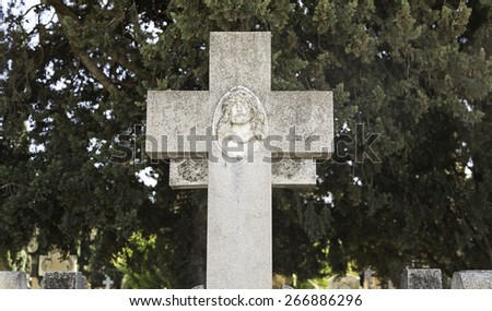 Religious cross on a grave, detail of an old cross in a cemetery - stock photo