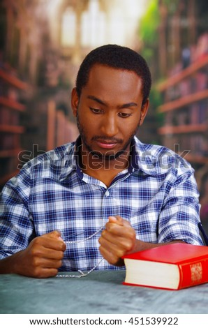 Religious man sitting and holding rosary looking down, red book lying on desk in front, religion concept - stock photo