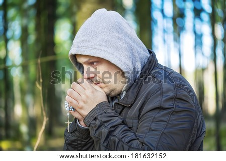 Religious man with a rosary in the woods  - stock photo