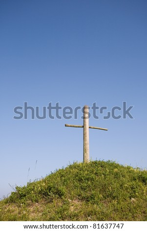Religious memorial cross on a beautiful green hill.