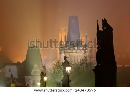 Religious sculptures and Gothic tower on the Charles bridge surrounded by thick fog at night, Prague, Czech Republic - stock photo