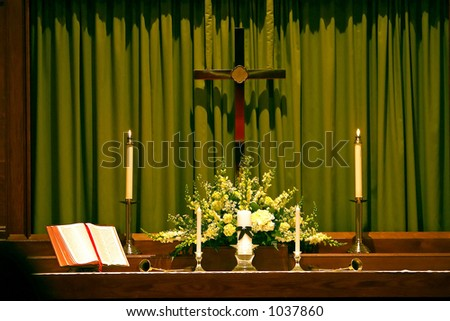 Religous altar that has a bible and candles on it with a cross hanging over it. - stock photo