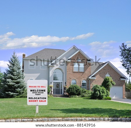 Relocation Short Sale Realtor Sign on Landscaped Front Yard Lawn of Suburban Home in Residential Neighborhood