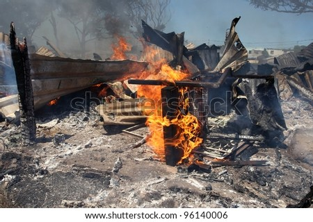 Remains of a burnt informal dwelling or shack house with a chair still burning - stock photo