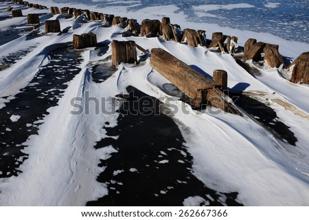remains of a wooden pier in the ice on lake, horizontal - stock photo