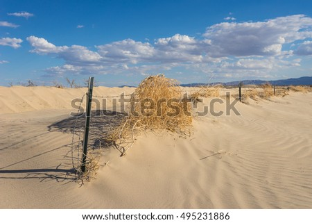Remains of barbed wire fence in sand dunes of southern California desert near Barstow.