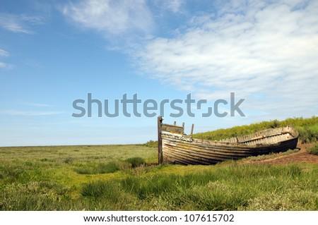 Remains of fishing boat on Norfolk coast at Blakeney - stock photo